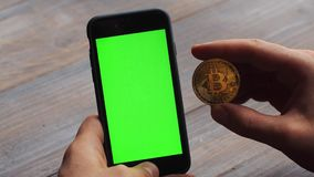 Man using vertical smartphone with green screen. Close-up shot of man`s hands with mobile phone and a gold bitcoin coin. Chroma key. Close up. Vertical stock footage