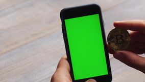 Man using vertical smartphone with green screen. Close-up shot of man`s hands with mobile phone and a gold bitcoin coin. Chroma key. Close up. Vertical stock video