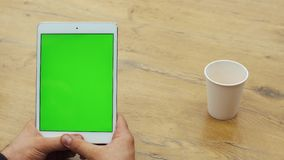 Man using vertical tablet with green screen. Close-up shot of man`s hands with tablet. Chroma key. Close up. Vertical.  stock video footage