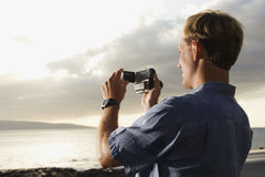 Man Using Video Camera at the Beach Royalty Free Stock Photos