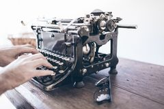 Man using vintage manual typewriter on rustic wooden table with motion blur due to carriage return stock photos