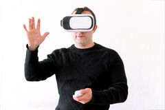 Man using a virtual glasses on white background. Young male business executive using virtual reality headset in office. Gays at office and using virtual Stock Image