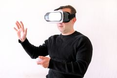 Man using a virtual glasses on white background. Young male business executive using virtual reality headset in office. Gays at office and using virtual Stock Photo
