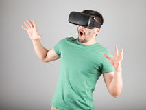Man using virtual reality glasses. Man with virtual reality glasses showing gesture isolated on a gray background Royalty Free Stock Image