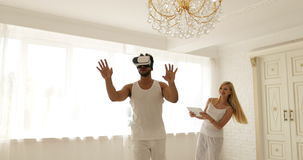 Man using virtual reality glasses woman holding digital tablet computer 3d technology concept, mix race couple home play stock footage