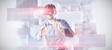 Composite image of man using virtual reality headset. Man using virtual reality headset against composite image of technology interface stock image