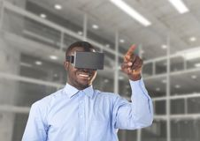 Man using virtual reality headset against office in background Royalty Free Stock Photo