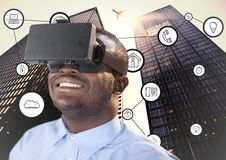 Man using virtual reality headset with connecting icons and skyscrapers in background Stock Images