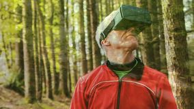 Man using a virtual reality headset. Digital composite of a Caucasian old man using a headset with a forest background stock video footage