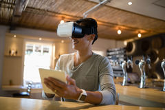 Man using virtual reality headset and digital tablet in restaurant Royalty Free Stock Images