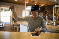 Man using virtual reality headset and digital tablet in restaurant Stock Photo