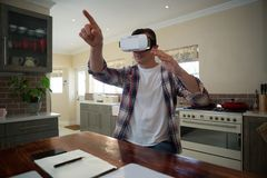 Man using virtual reality headset in kitchen. At home Royalty Free Stock Photos
