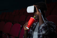 Man using virtual reality headset while watching movie. In theatre Royalty Free Stock Photo