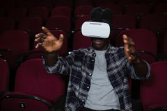 Man using virtual reality headset while watching movie. In theatre Royalty Free Stock Image
