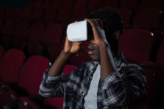 Man using virtual reality headset while watching movie. In theatre Stock Photo