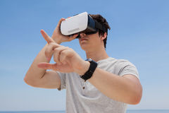 Man using vr headset against the blue sky. Close-up of man using vr headset against the blue sky Stock Photo