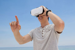 Man using vr headset against the blue sky. Close-up of man using vr headset against the blue sky Royalty Free Stock Photo