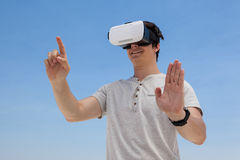 Man using vr headset against the blue sky. Close-up of man using vr headset against the blue sky Stock Photos