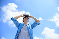 Man using VR headset glasses. Smile happy man getting experience using VR-headset glasses of virtual reality with sky and cloud background, asian male Royalty Free Stock Photography