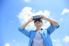Man using VR headset glasses. Smile happy man getting experience using VR-headset glasses of virtual reality with sky and cloud background, asian male Stock Photo