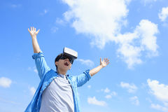 Man using VR headset glasses. Smile happy man getting experience using VR-headset glasses of virtual reality with sky and cloud background, asian male Royalty Free Stock Photo