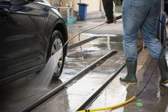 Man Using Water Pressure Machine to Wash a Car royalty free stock photo