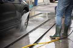 Man Using Water Pressure Machine to Wash a Car stock photos