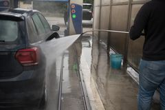 Man Using Water Pressure Machine to Wash a Car royalty free stock images
