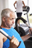 Man Using Weights Machine With Runner On Treadmill In Background Stock Photos