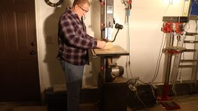 Man using a wood-cutting bandsaw to shape a circle for turning a bowl. Skilled craftsman using a wood bandsaw to cut a blank into a circle for turning into a stock footage