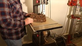 Man using a wood-cutting bandsaw to shape a circle for turning a bowl stock video footage