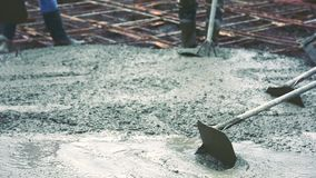 Man using a wooden spatula for cement after Pouring ready-mixed concrete. On steel reinforcement to make the road by mixing mobile the concrete mixer stock video footage