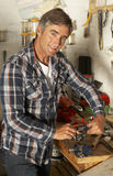 Man Using Workbench In Garage Royalty Free Stock Image