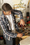 Man Using Workbench In Garage Stock Photo