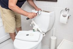Man using wrench repairing toilet cistern. In a concept of DIY repairs with copy space stock photos