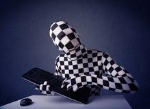 Man utan identiteten som arbetar med tangentbordet på blå bakgrund Arkivbild
