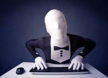 Man utan identiteten som arbetar med tangentbordet på blå bakgrund Arkivbilder