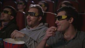 Man vänner som äter popcorn på filmen för bion 3d Män har gyckel på bion stock video