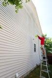 Man våren som gör ren sidorna av ett hus fotografering för bildbyråer