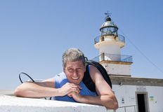 Man on vacation in front of a lighthouse Stock Images