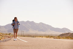 Man On Vacation Hitchhiking Along Country Road Royalty Free Stock Images