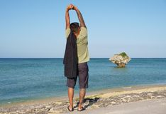 Man on vacation in Japan 2. Man on seawall on vacation in Japan with T shirt stretching Stock Photography