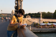 Man on vacations. Young man on vacations in Paris, relaxing over the Alexander the 3rd bridge Royalty Free Stock Photos