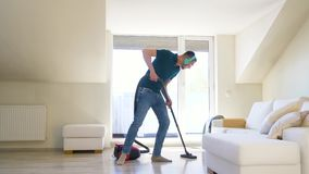Man with vacuum cleaner and headphones at home. Household, housework and music concept - happy man with vacuum cleaner and headphones cleaning floor and having stock video footage
