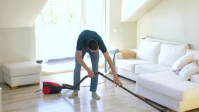 Man with vacuum cleaner at home. Household and cleaning concept - man with vacuum cleaner at home stock video
