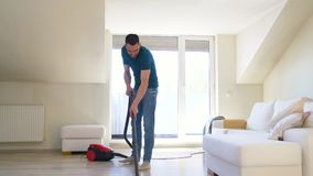 Man with vacuum cleaner at home. Household and cleaning concept - man with vacuum cleaner at home stock footage