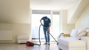 Man with vacuum cleaner at home. Household and cleaning concept - man with vacuum cleaner at home stock video footage