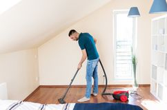Man with vacuum cleaner at home. Household, housework and cleaning concept - happy man with vacuum cleaner at home stock photography