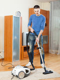 Man with vacuum cleaner  in living room Royalty Free Stock Photography