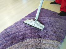 Man vacuuming the carpet in the room. Cleaningn Royalty Free Stock Images
